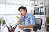 Young Asian businessmen have a headache from hard work.