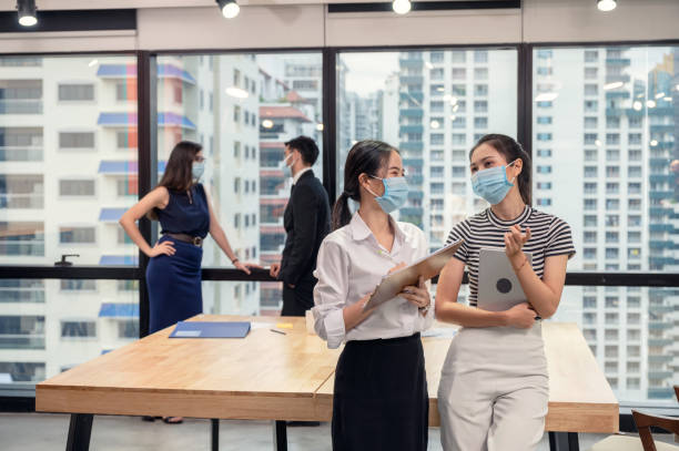 Young asian businesswoman colleague wearing face mask and talking in new normal office, Caucasian executive discussing on behind stock photo
