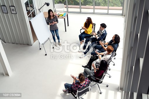 1031237974 istock photo Young asian businesswoman explain idea to group of creative diverse team at modern office. Wide top view of manager standing against multiethnic people. Audience applauding speaker after presentation. 1031232694