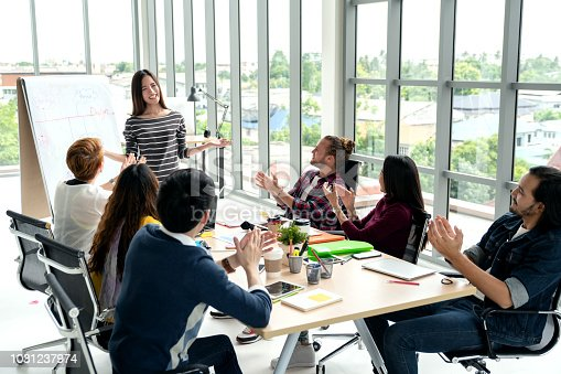 1031237974 istock photo Young asian businesswoman explain idea to group of creative diverse team at modern office. Manager standing against rear view of multiethnic people. Audience applauding speaker after presentation. 1031237974