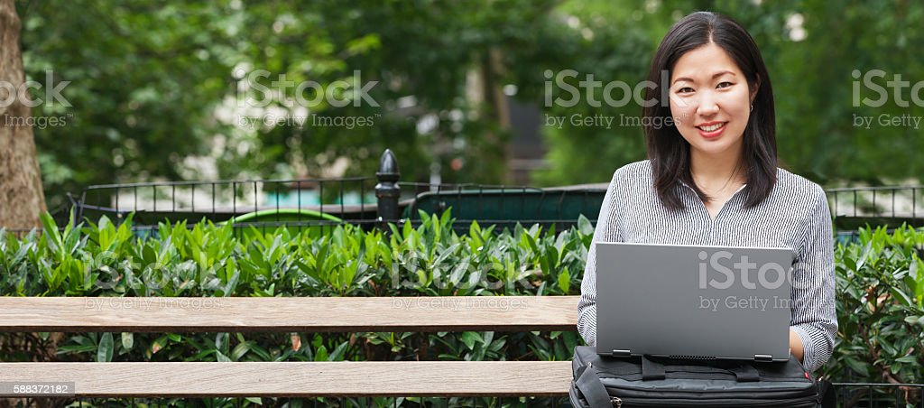 young Asian businesswoman sitting on park bench working on laptop stock photo