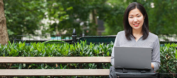 young Asian businesswoman sitting on park bench working on laptop beautiful young Asian businesswoman working on her computer in a city public park. great for banner korean ethnicity stock pictures, royalty-free photos & images
