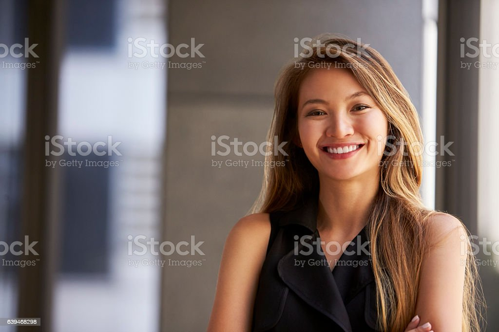 Young Asian businesswoman smiling to camera, close up stock photo