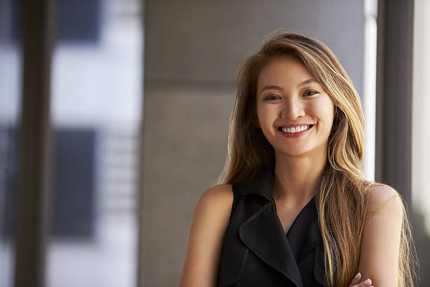 Young Asian businesswoman smiling to camera, close up 스톡 사진