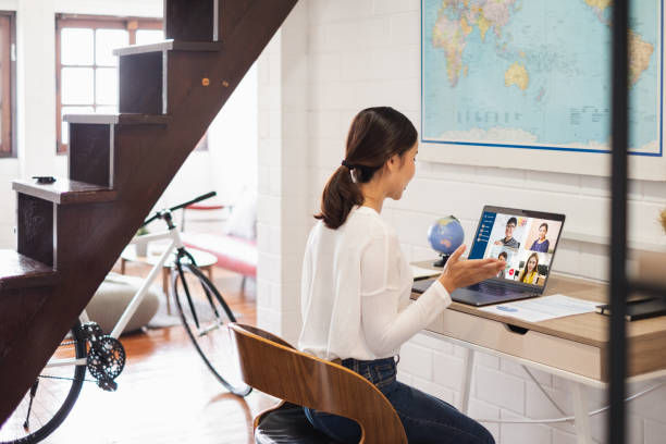 Young Asian businesswoman work at home and virtual video conference meeting with colleagues business people, online working, video call due to social distancing at home office stock photo