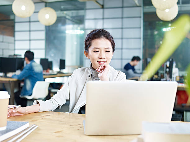 young asian businesswoman working in office - japanese culture stock pictures, royalty-free photos & images