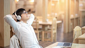 Young Asian carefree guy with glasses enjoy listening to music by headphones relaxing after working with laptop computer in the cafe. Online music application and entertainment media concepts