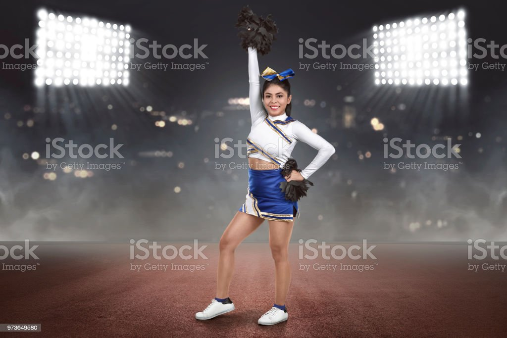 Young asian cheerleader action with pom-poms stock photo