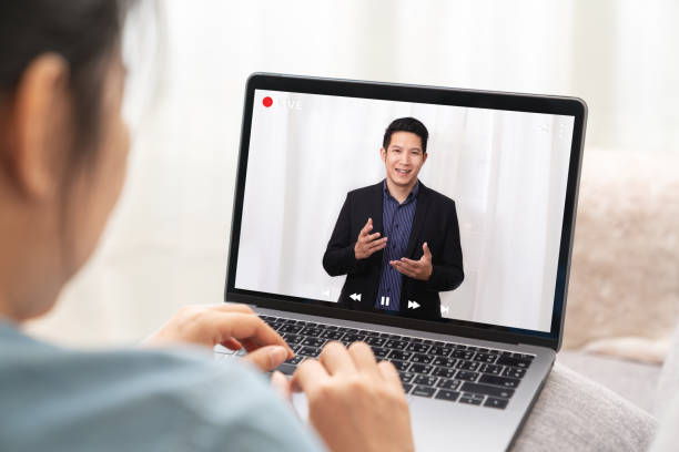 Young asian chinese leader or businessman on management forum, teleconference, town hall or press video conference online with work remotely at home during coronavirus and business continuity concept. stock photo