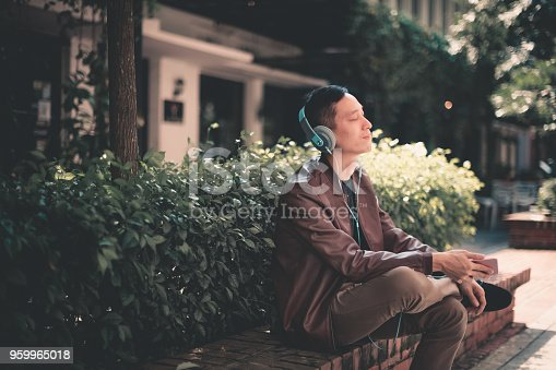 istock young asian chinese male sitting down and listening to music 959965018