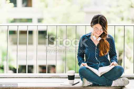 istock Young Asian college student girl reading book for exam, sitting at university campus with copy space. Education or casual studying lifestyle concept 961043410
