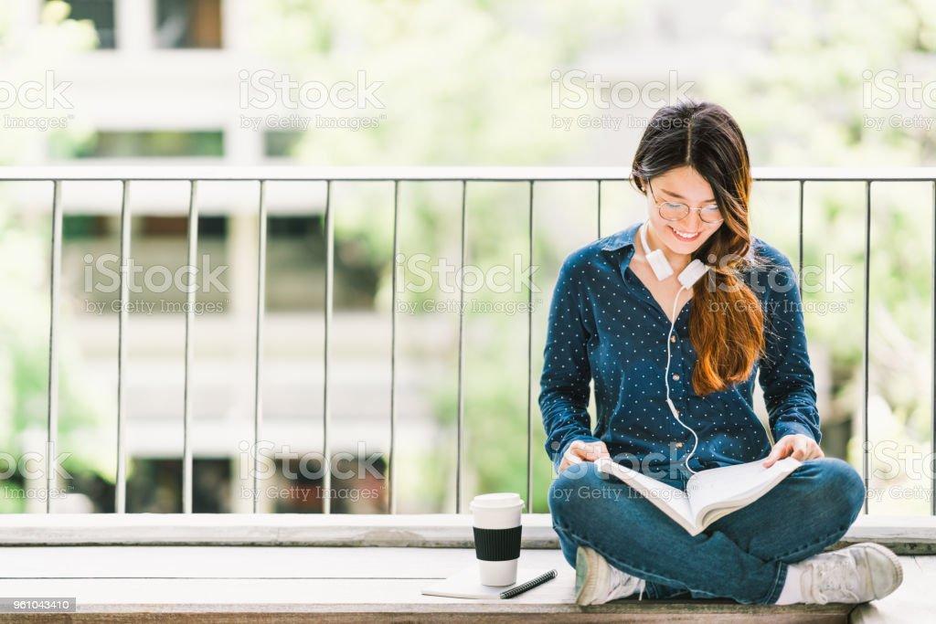 年輕的亞洲大學生女孩看書考試, 坐在大學校園裡複印空間。教育或休閒學習生活方式概念圖像檔
