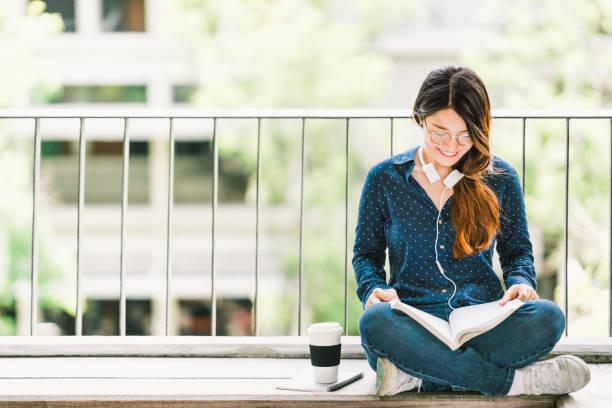 コピー スペースで大学キャンパスに座って受験本を読んで若いアジア大学学生の女の子。教育やカジュアルな勉強のライフ スタイル コンセプト - 勉強する ストックフォトと画像