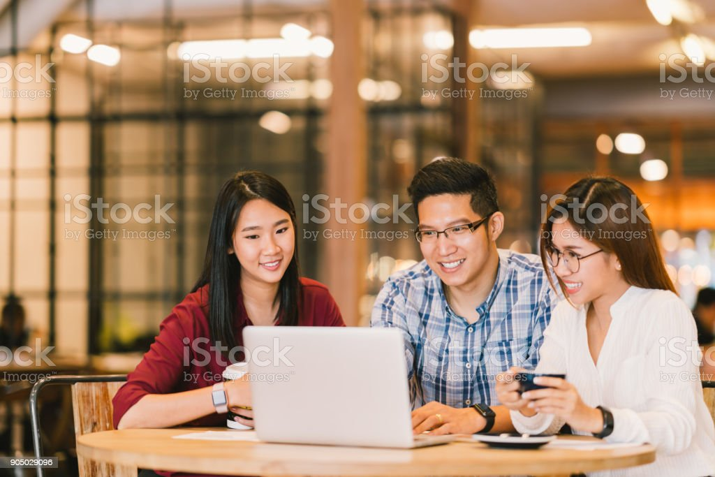 Young Asian college students group or coworkers using laptop computer together at cafe or university. Casual business, freelance work, coffee break meeting, e-learning or e-commerce activity concept stock photo