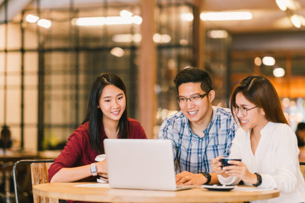 若いアジア大学生グループやカフェや大学で一緒にパソコンを使用して同僚。カジュアルなビジネス、フリーランスの仕事、コーヒーブレイク ・ ミーティング、e-ラーニングや電子商取引の活動の概念 - 大学生 パソコン 日本 ストックフォトと画像