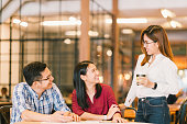 アジアの若い大学生学生や同僚懇話会、喫茶店、多様なグループです。カジュアルなビジネス、カフェ、または教育コンセプトでフリーランスの仕事