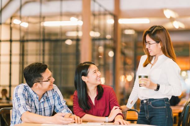 アジアの若い大学生学生や同僚懇話会、喫茶店、多様なグループです。カジュアルなビジネス、カフェ、または教育コンセプトでフリーランスの仕事 - 挨拶 ストックフォトと画像