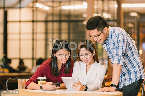 istock Young Asian college students or coworkers using digital tablet and smartphone together at coffee shop, diverse group. Casual business, freelance work at cafe, social meeting, or education concept 821679364