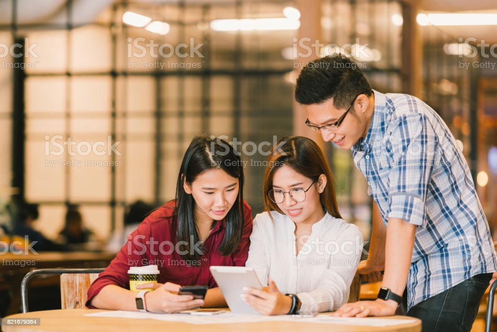 Young Asian college students or coworkers using digital tablet and smartphone together at coffee shop, diverse group. Casual business, freelance work at cafe, social meeting, or education concept stock photo