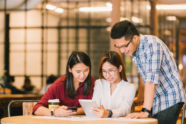 アジア大学生や同僚、喫茶店、多様なグループ デジタル タブレットとスマート フォンを一緒に使用します。カジュアルなビジネス、カフェ、会議、または教育コンセプトでフリーランスの仕事 - スマートカジュアル ストックフォトと画像