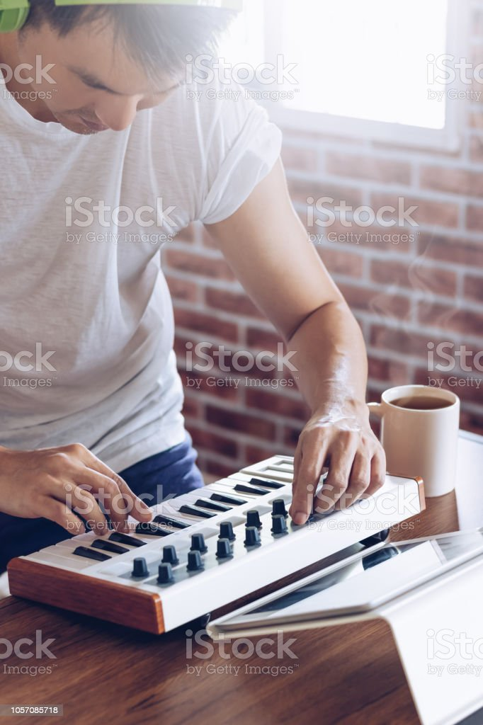young asian composer making music in bedroom studio. man enjoy...