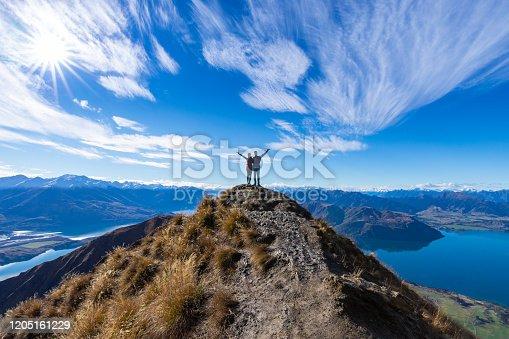 Young Asian couple celebrating success at Roy's Peak Lake Wanaka New Zealand