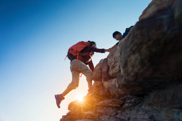 Young asian couple climbing up on the mountain stock photo