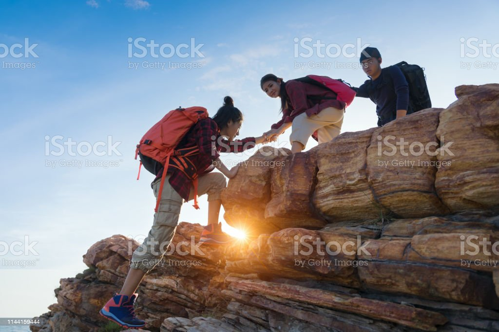 Young asian couple climbing up on the mountain,hiking and team work...