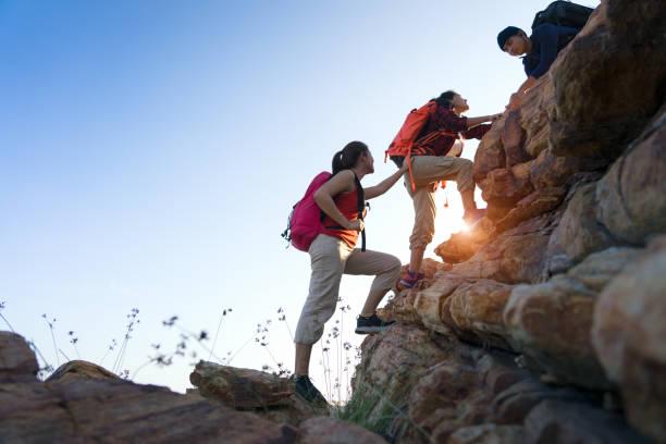 Junges asiatisches Ehepaar klettert auf den Berg, Wandern und Team-Arbeitskonzept. – Foto