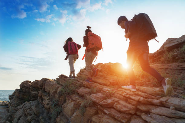 Young asian couple climbing up on the mountain,hiking and team work concept. stock photo