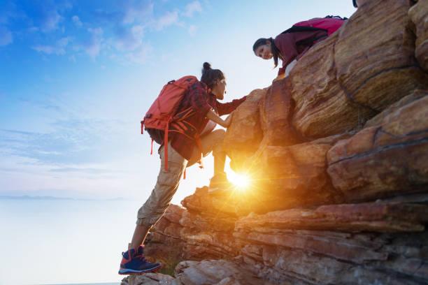 Junge asiatische Paar Klettern auf dem Berg, Wandern und Team-Work-Konzept. – Foto