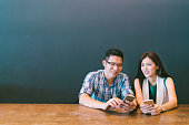 Young Asian couple, college students, or coworkers using smartphone together at cafe, modern lifestyle with gadget technology or love and relationship concept, with copy space
