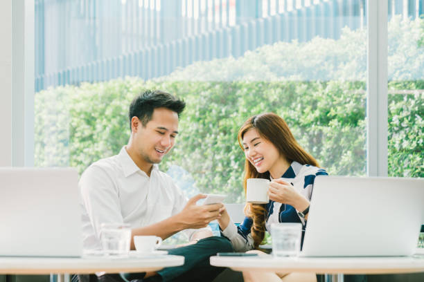 Young Asian couple, coworkers, or business partners have fun using smartphone together, with laptop computer at coffee shop. Information technology, cafe lifestyle, or romantic relationship concept stock photo