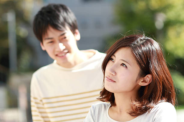 young asian couple deep in thought - 異性情侶 個照片及圖片檔