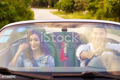 817334706 istock photo young asian couple driving a sports car 817339554