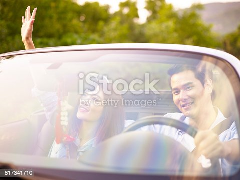 817334706 istock photo young asian couple driving a sports car 817341710