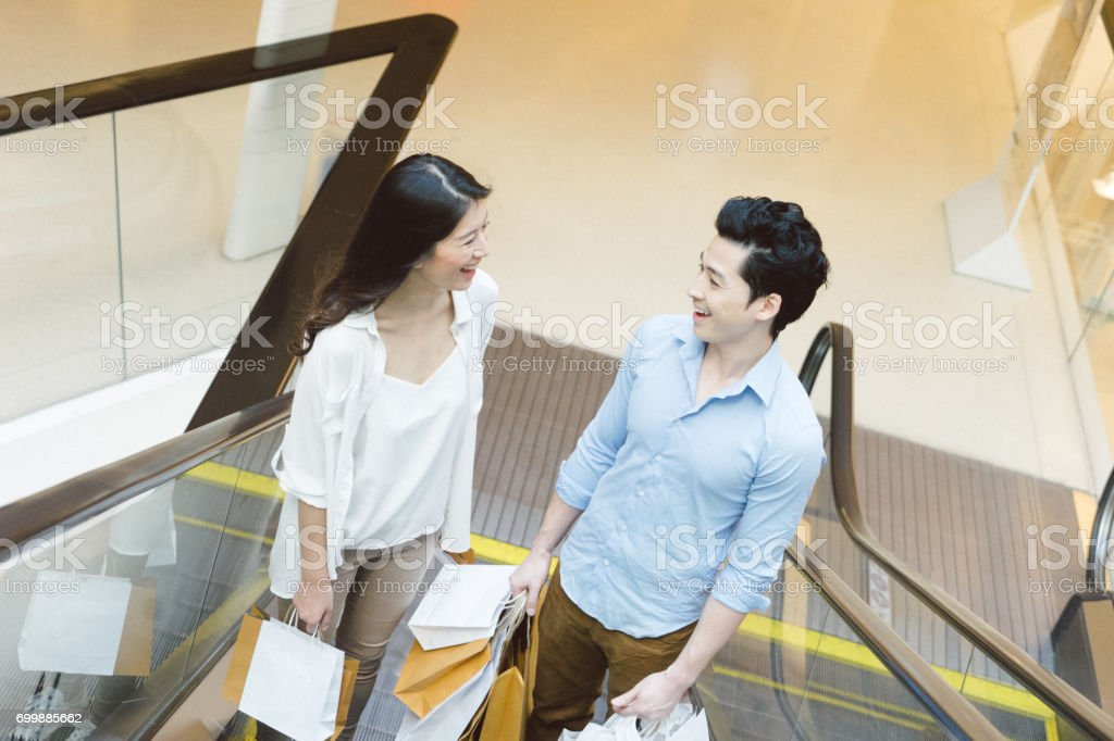Young asian couple enjoying shopping in the mall stock photo