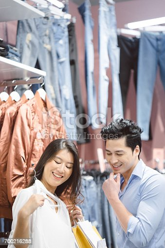 Young asian couple enjoying shopping in the mall, they are in a store trying on clothes, talking and smiling