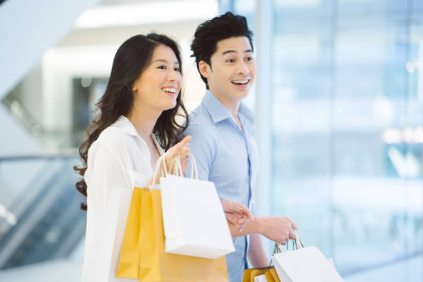 Young asian couple enjoying shopping in the mall Young asian couple enjoying shopping in the mall, they are walking and talking with paper bags in their hands shopping couple asian stock pictures, royalty-free photos & images