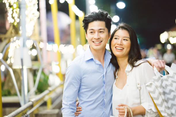 Young asian couple enjoying shopping in the night market Young asian couple enjoying shopping in the night market, they are walking around, taking and smiling shopping couple asian stock pictures, royalty-free photos & images