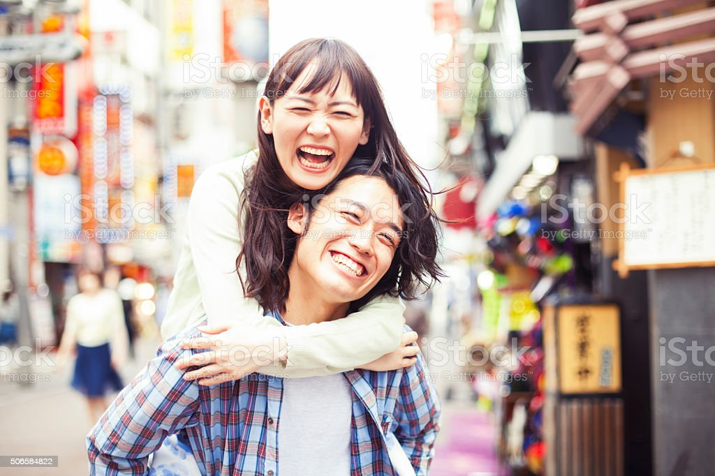 Young asian couple having fun Happy young asian couple having a great fun with piggy back . Image taken during Tokyo Istockalypse 2015 20-29 Years Stock Photo