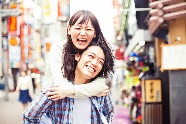 Young asian couple having fun Happy young asian couple having a great fun with piggy back . Image taken during Tokyo Istockalypse 2015 only japanese stock pictures, royalty-free photos & images