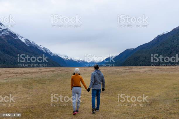 Photo of Young Asian couple holding hands walking into mountain Eglinton valley Fiordland National Park New Zealand