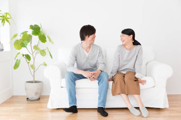 リビング ライフ スタイル イメージで若いアジアのカップル - ソファ ストックフォトと画像