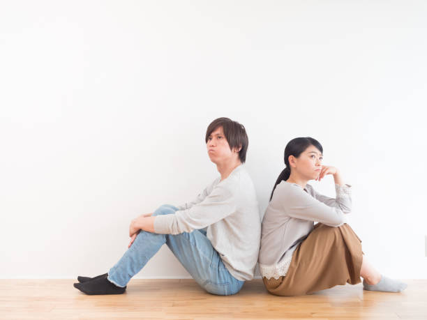 young asian couple in living room lifestyle image young asian couple in living room lifestyle image asian couple arguing stock pictures, royalty-free photos & images