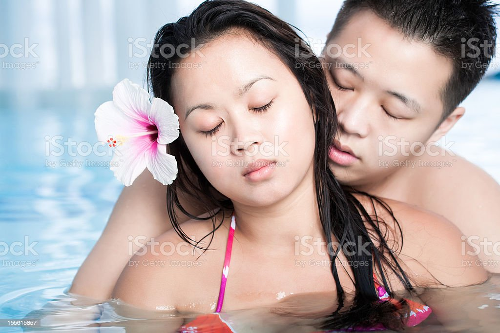 Young asian couple in the pool royalty-free stock photo