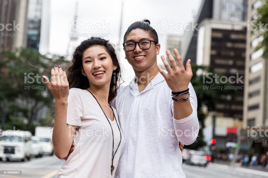 Young Asian Couple Inviting Someone to Come stock photo