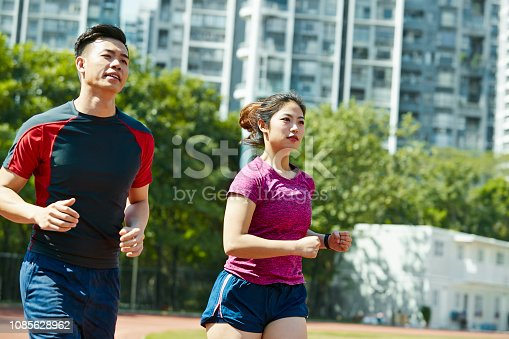 young asian man and woman training running on track in stadium