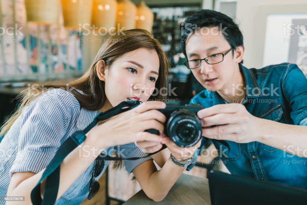 Young Asian couple learning to use mirrorless digital camera together at coffee shop, modern gadget technology concept, focus on the girl, depth of field effect stock photo