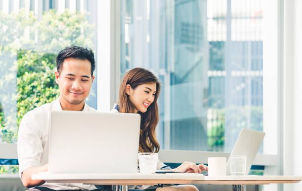 若いアジアのカップルや大学学生のコーヒー ショップや大学キャンパスでラップトップ コンピューターのノートブック作業を一緒に使用します。情報技術、ライフ スタイル カフェ、オフィスでのミーティング、または e ラーニングの概念 - 大学生 パソコン 日本 ストックフォトと画像